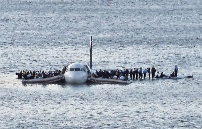 Airline passengers wait to be rescued on the wings of a US Airways Airbus A320 jetliner.