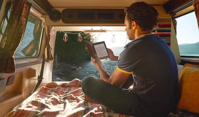 A person reading from a Kindle while car camping