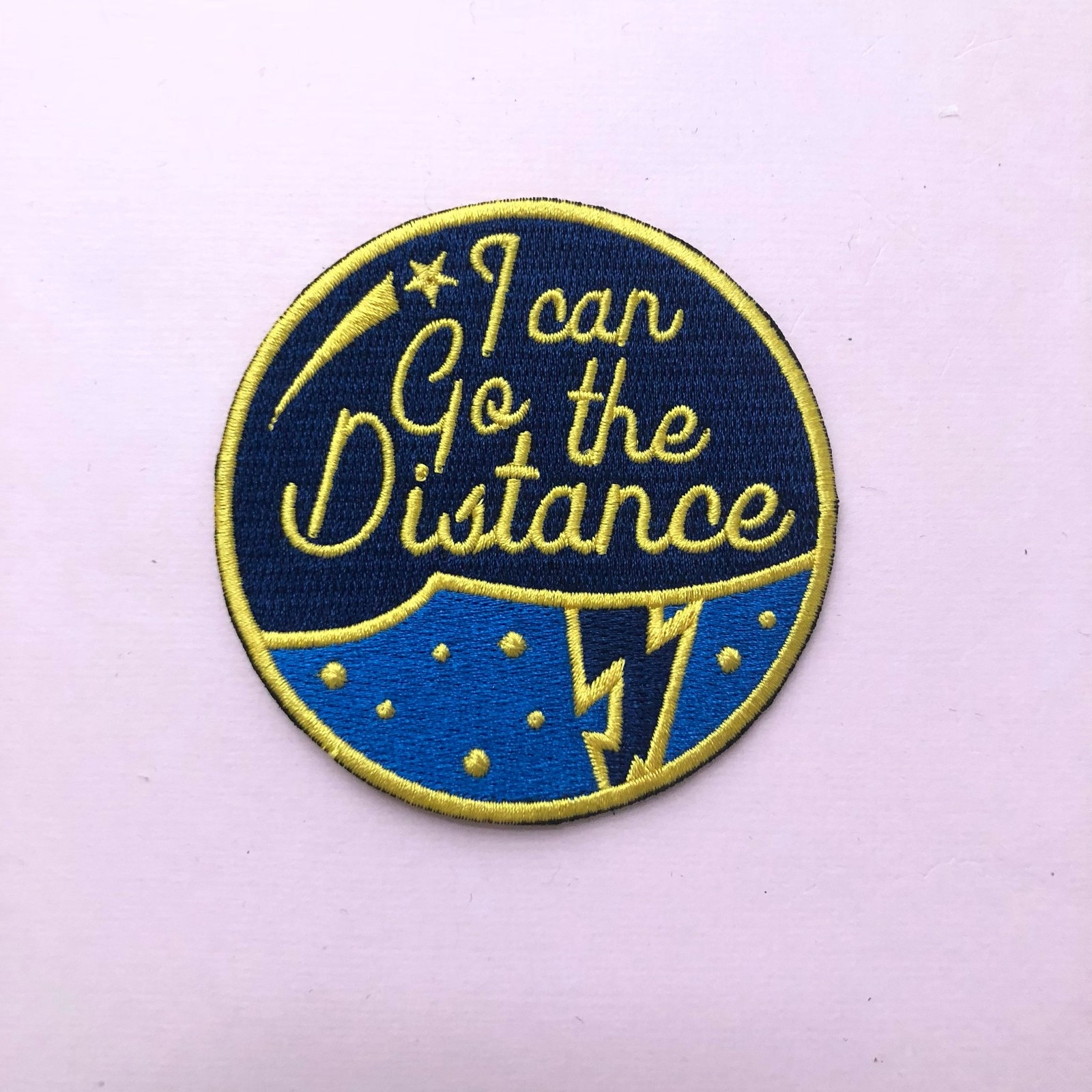 """a round patch that says """"i can go the distance"""" with a lightning bolt under it"""