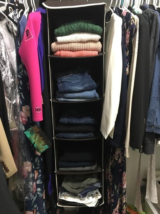 A reviewer's folded clothes in the organizer hanging in the closet