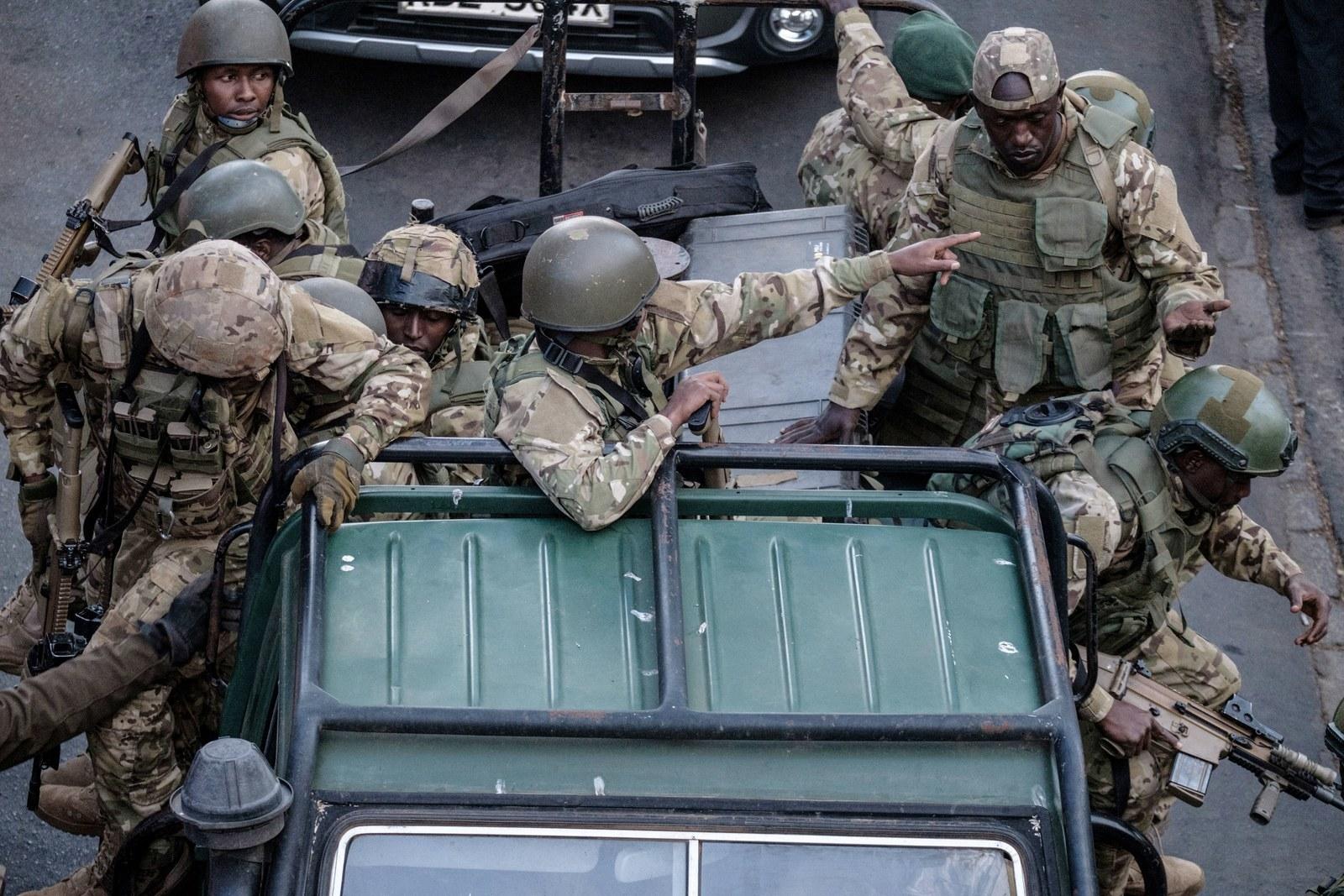 Kenyan security forces get out of a car after a blast followed by a gun battle.