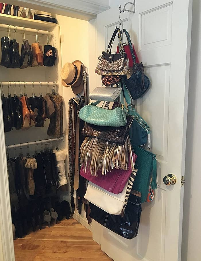 a collection of purses hanging on the bag organizer attached to the back of a closet door