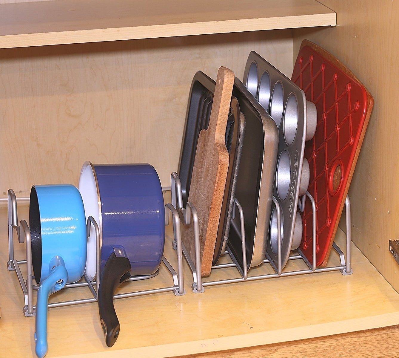 the bakeware rack in a cabinet holding two pots and some baking trays