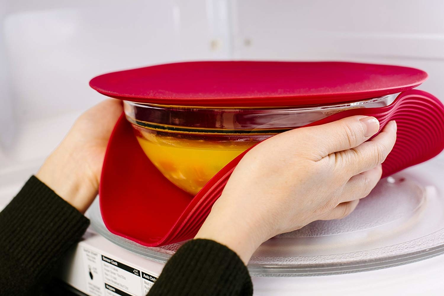 A person grabbing something out of the microwave with Safe Grabs