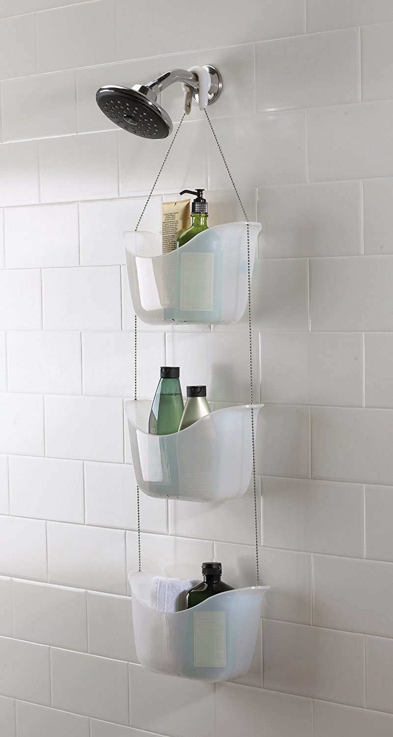 the three tier shower caddy in white hanging from a shower head