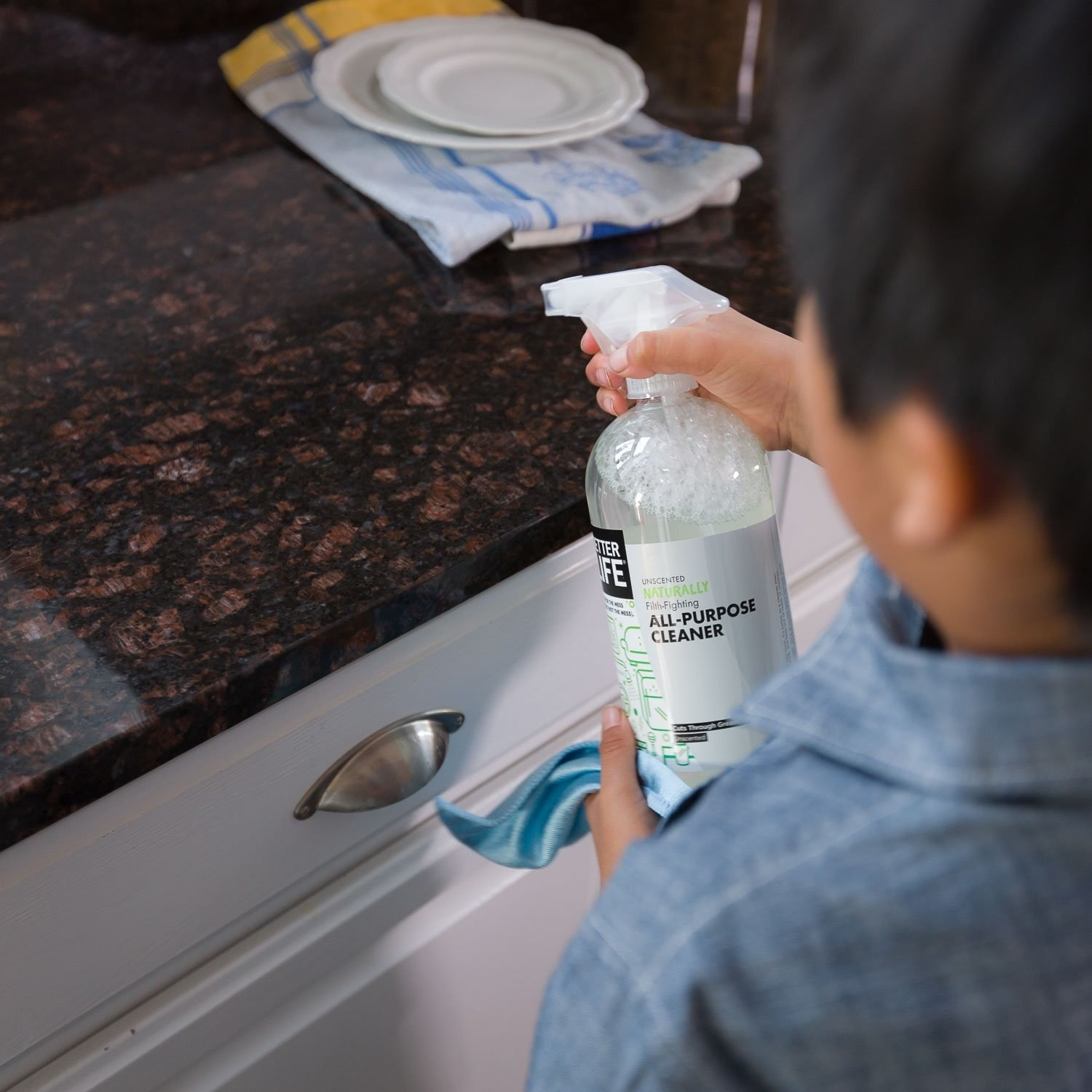 A kid cleaning the counter with the all-purpose cleaner
