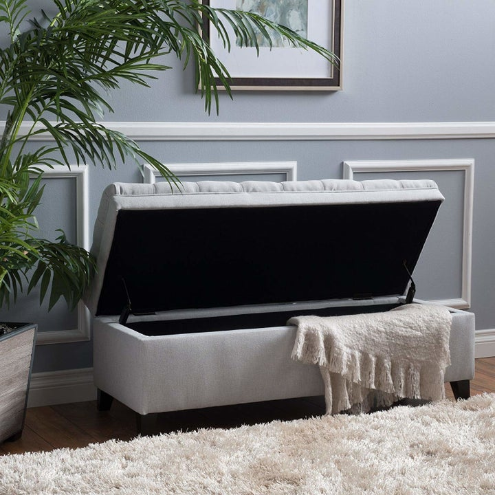 The ottoman with the top open and a blanket inside