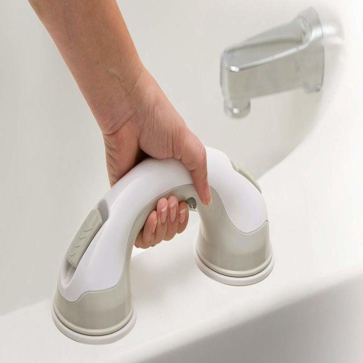 hand gripping handle on bathtub ledge