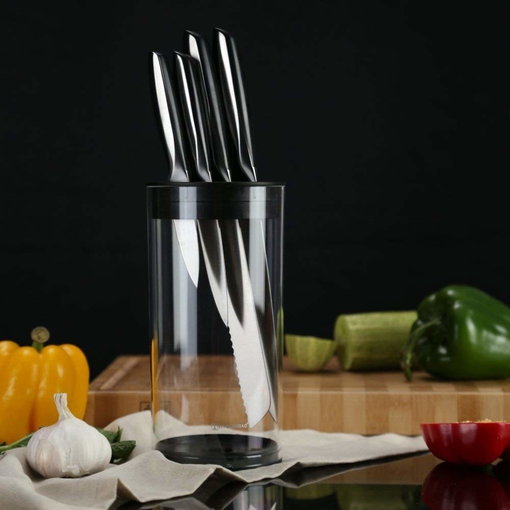 the cylindrical transparent knife block holding a set of four knives
