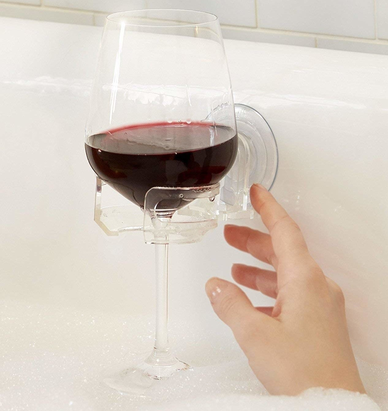 hand reaching for wine glass in clear suction cup bathtub holder