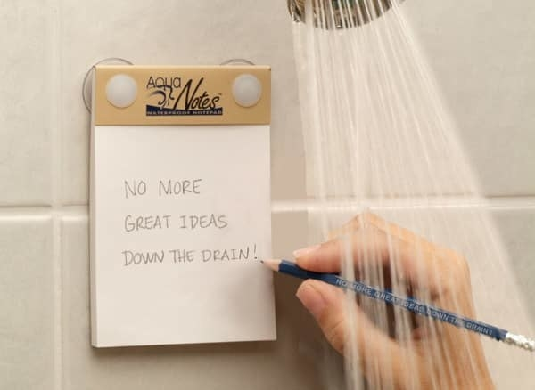 "hand writing ""no more great ideas down the drain"" on notepad in shower"