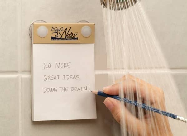 """hand writing """"no more great ideas down the drain"""" on notepad in shower"""