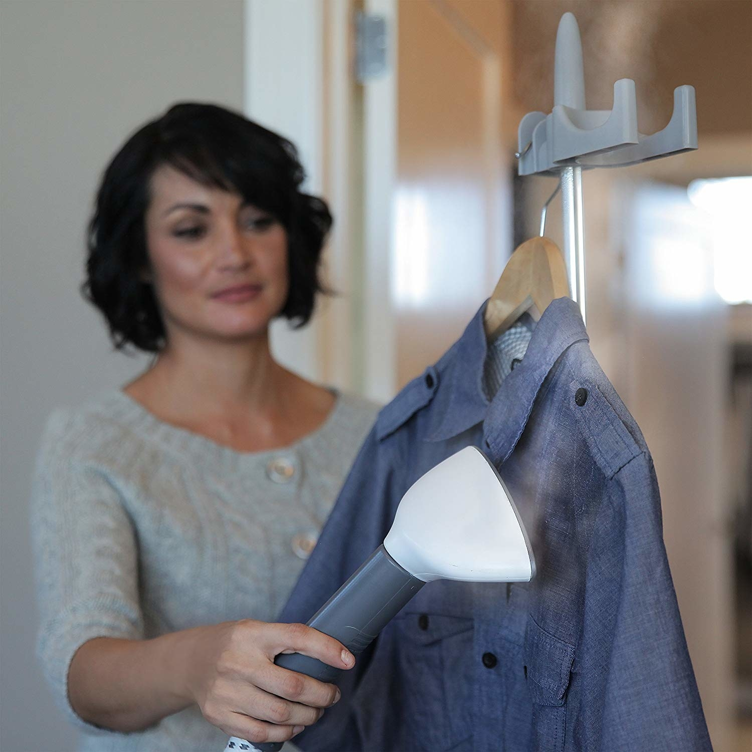 A person steaming a button-down shirt they've hung at the top of the steamer