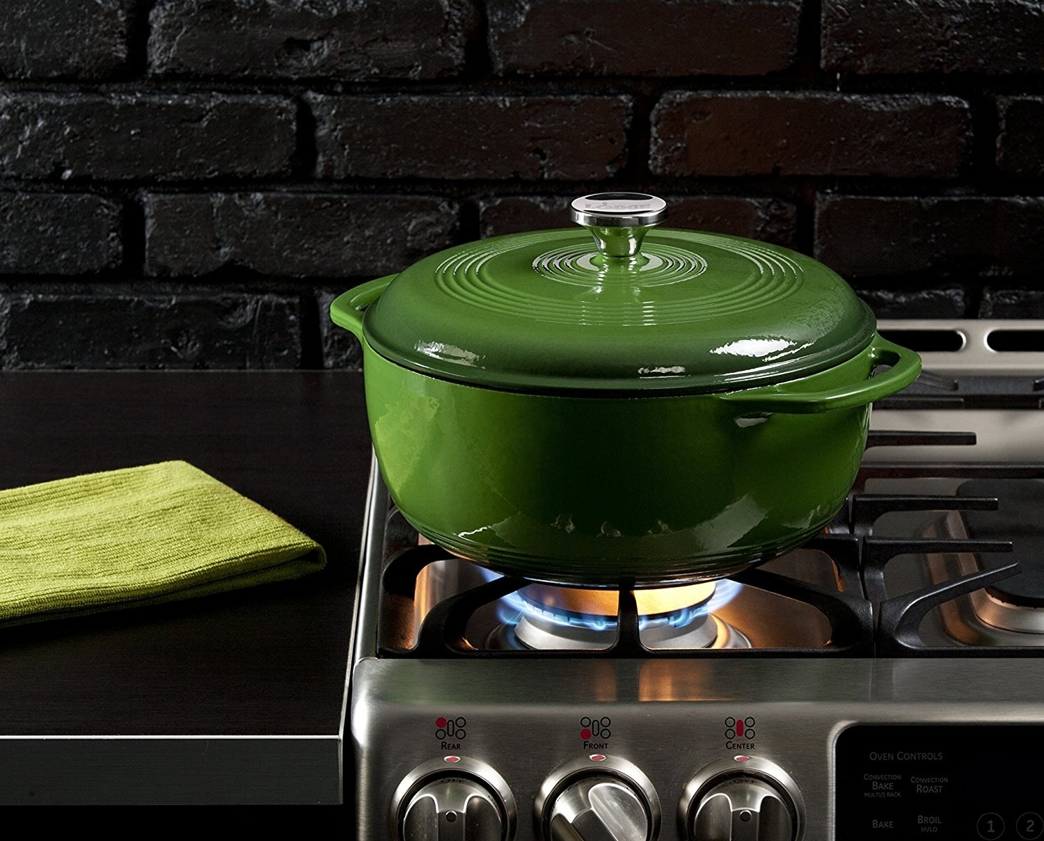An action shot of the cast iron pot cooking food over an open-flame stovetop