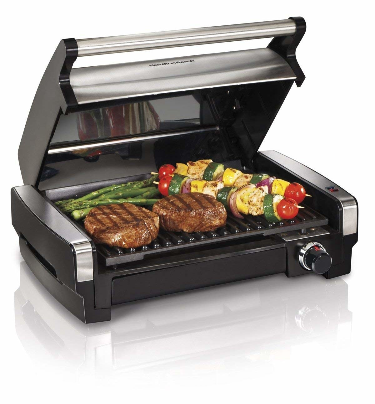 Small portable grill with two steaks, two kababs, and some asparagus being cooked