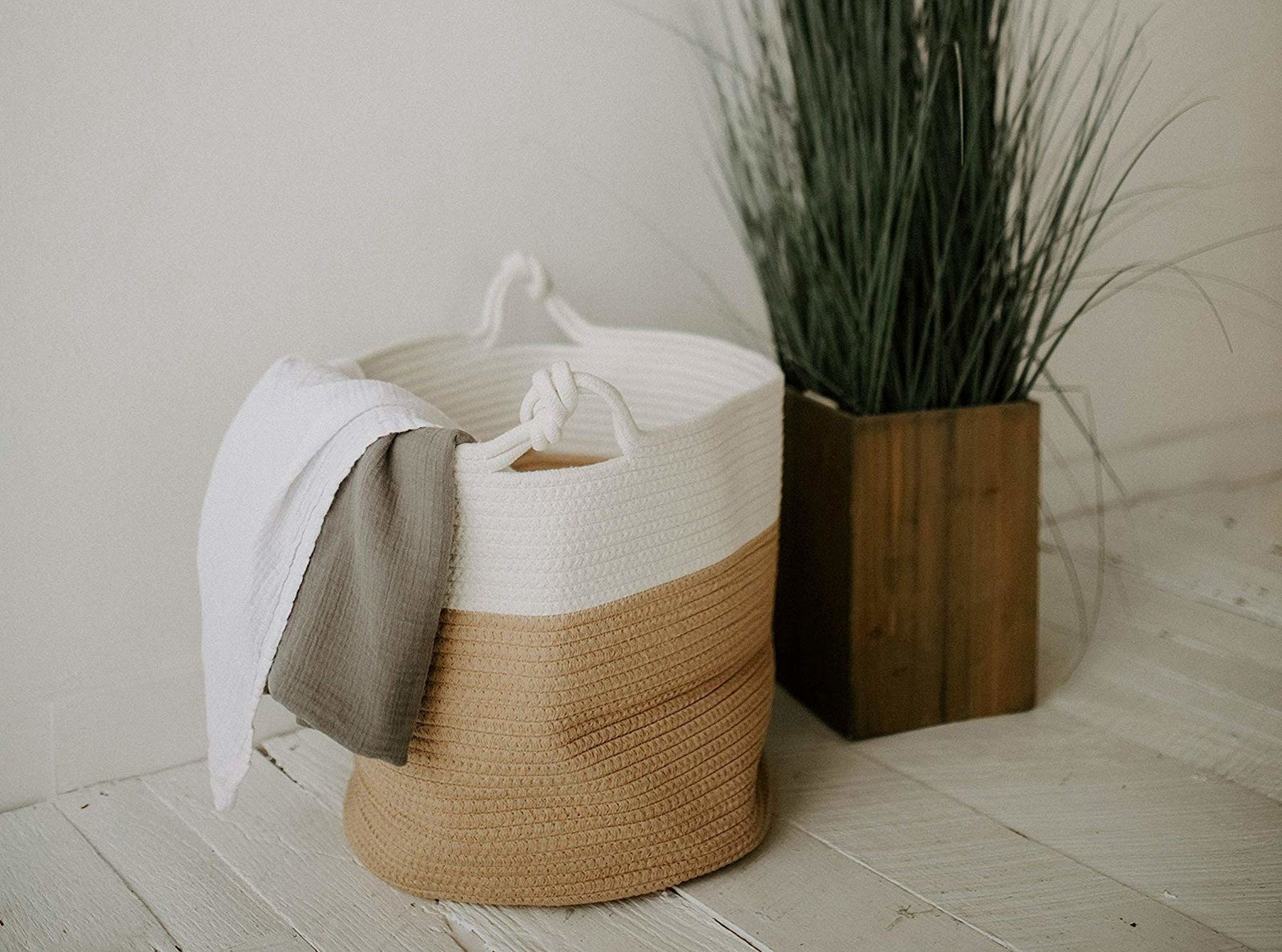 a woven two-tone basket filled with a blanket