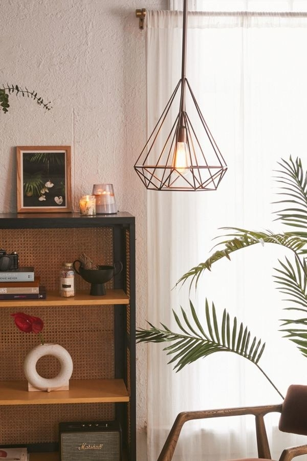 a bronze pendant light with a diamond-shaped cage around it