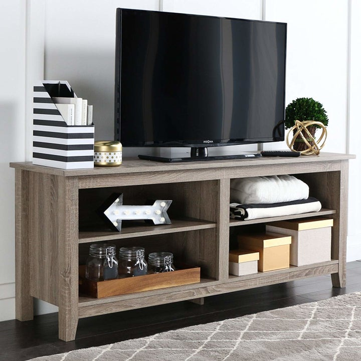 a wooden tv stand with four shelves in it
