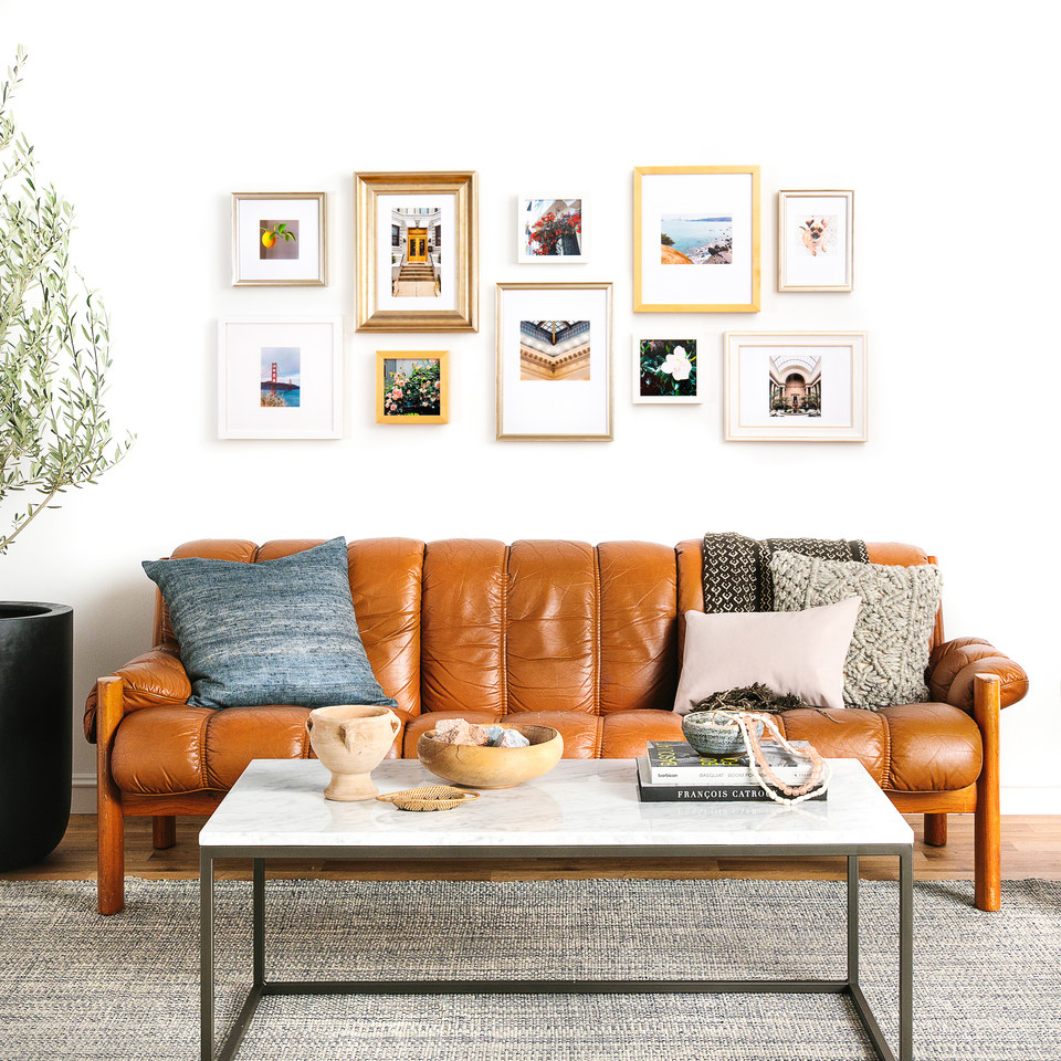 an array of frames behind a couch