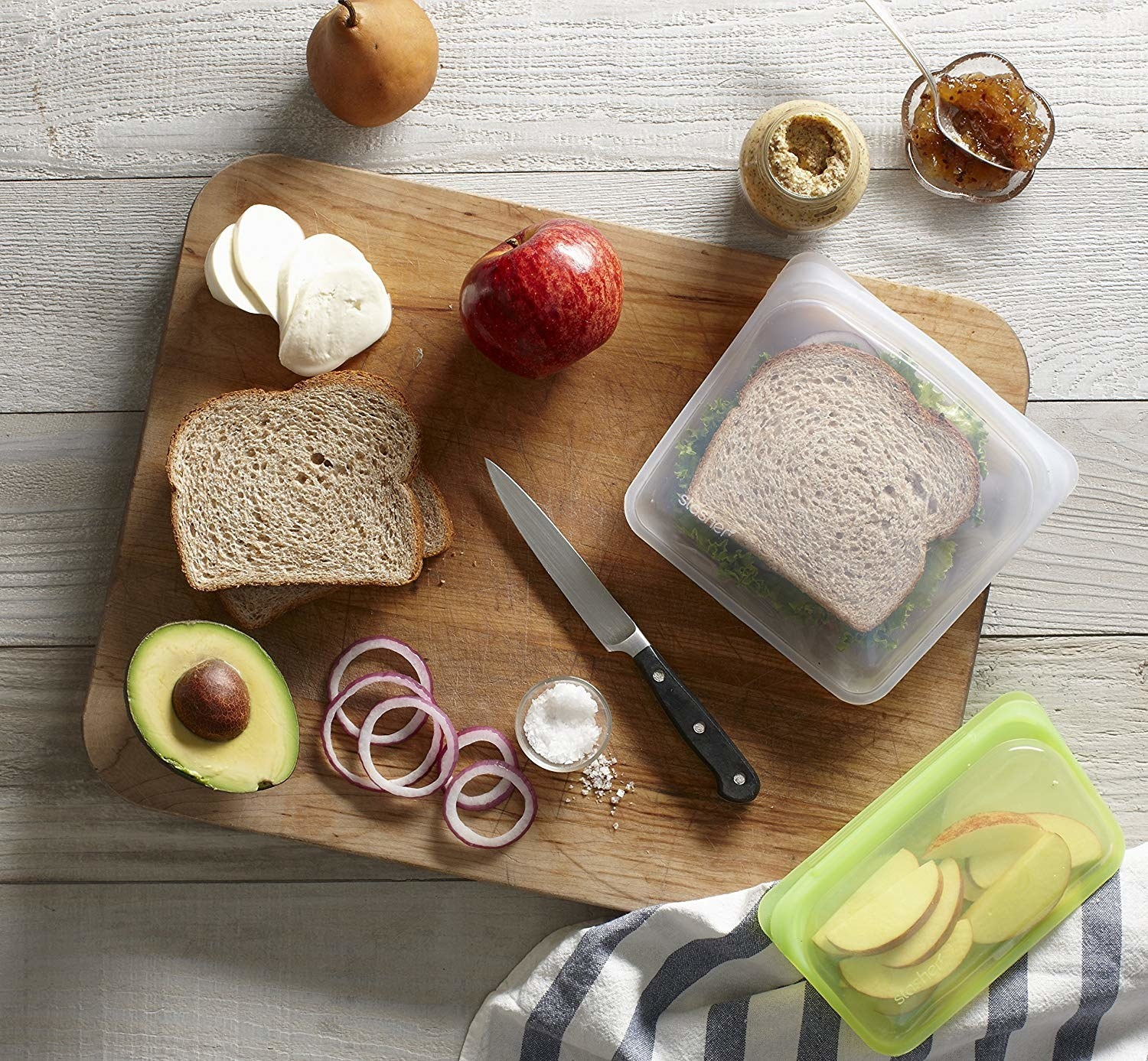 Sandwich being prepped with another inside storage bag. A smaller one holds apple slices.