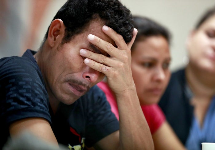 Melvin, who was separated from their child, listens as they hear other immigrants tell of their separation from their children at the border.