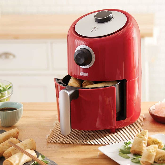 The air fryer in red, featuring an analog timer, round temperature dial, and convenient handle for removing the basket
