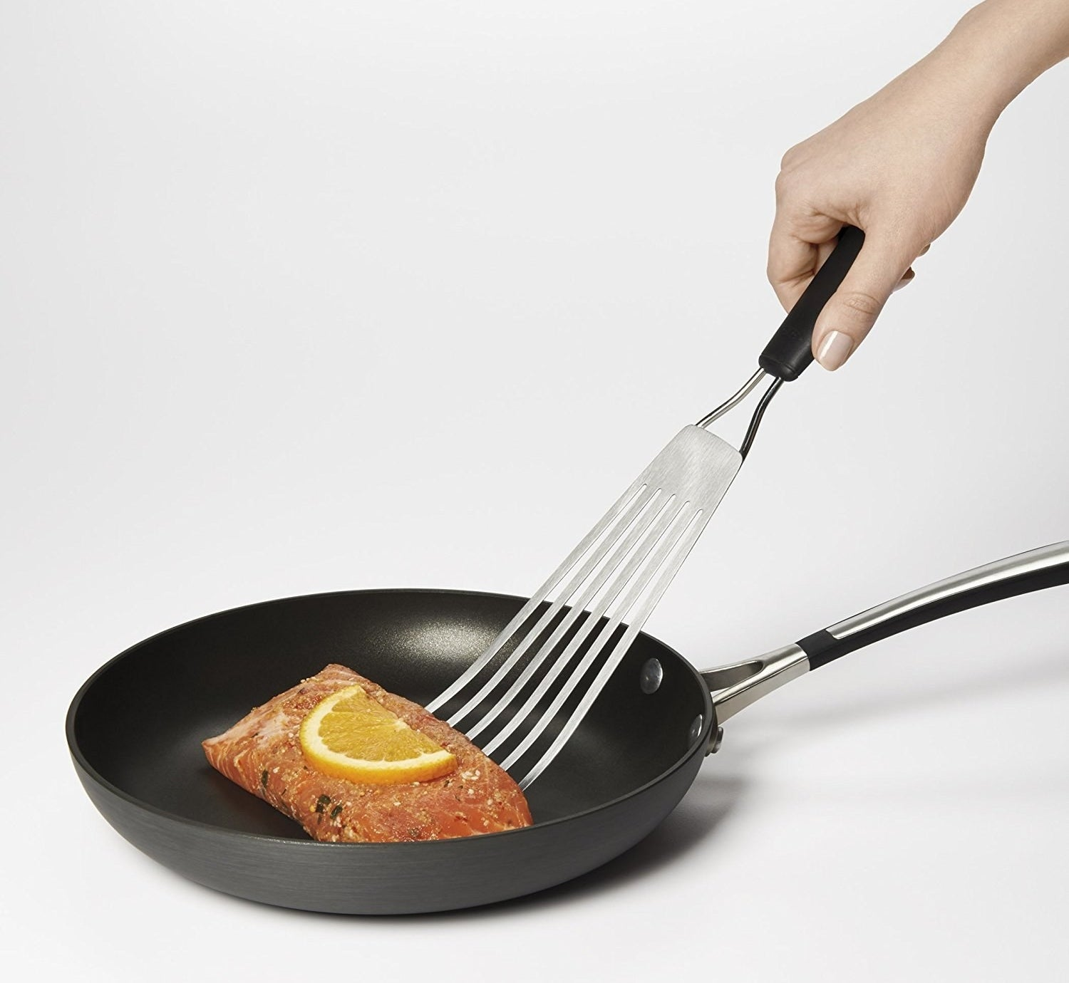The spatula is being used to flip fish