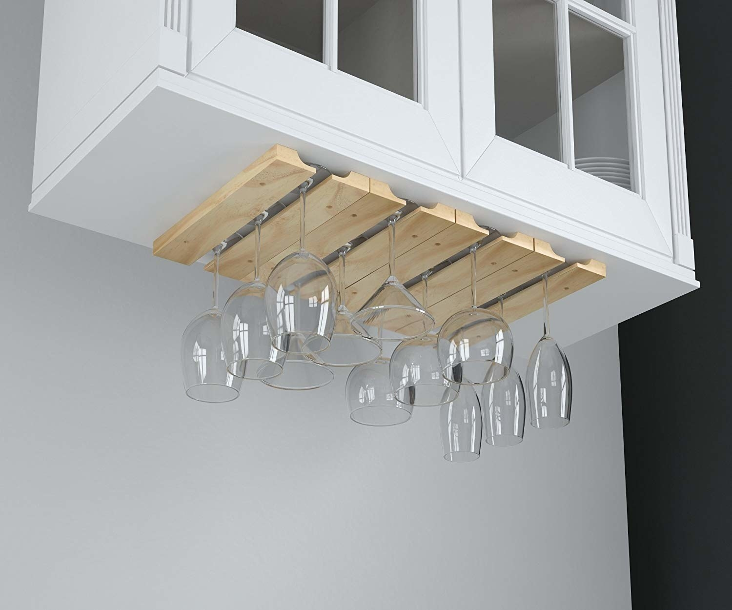 Wine glasses hanging upside down on mounted wooden rack