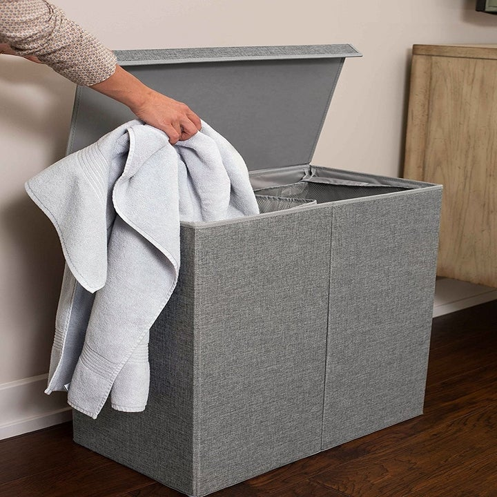 the laundry hamper in grey opened with a hand putting a towel into one side of it