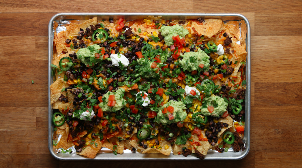 After that, he adds smashed avocado, cilantro, scallions, and a slew of fresh toppings to take these nachos to the next level. -  They're simple, flavorful, a great thing to snack on during the big game — and easy to make, too!