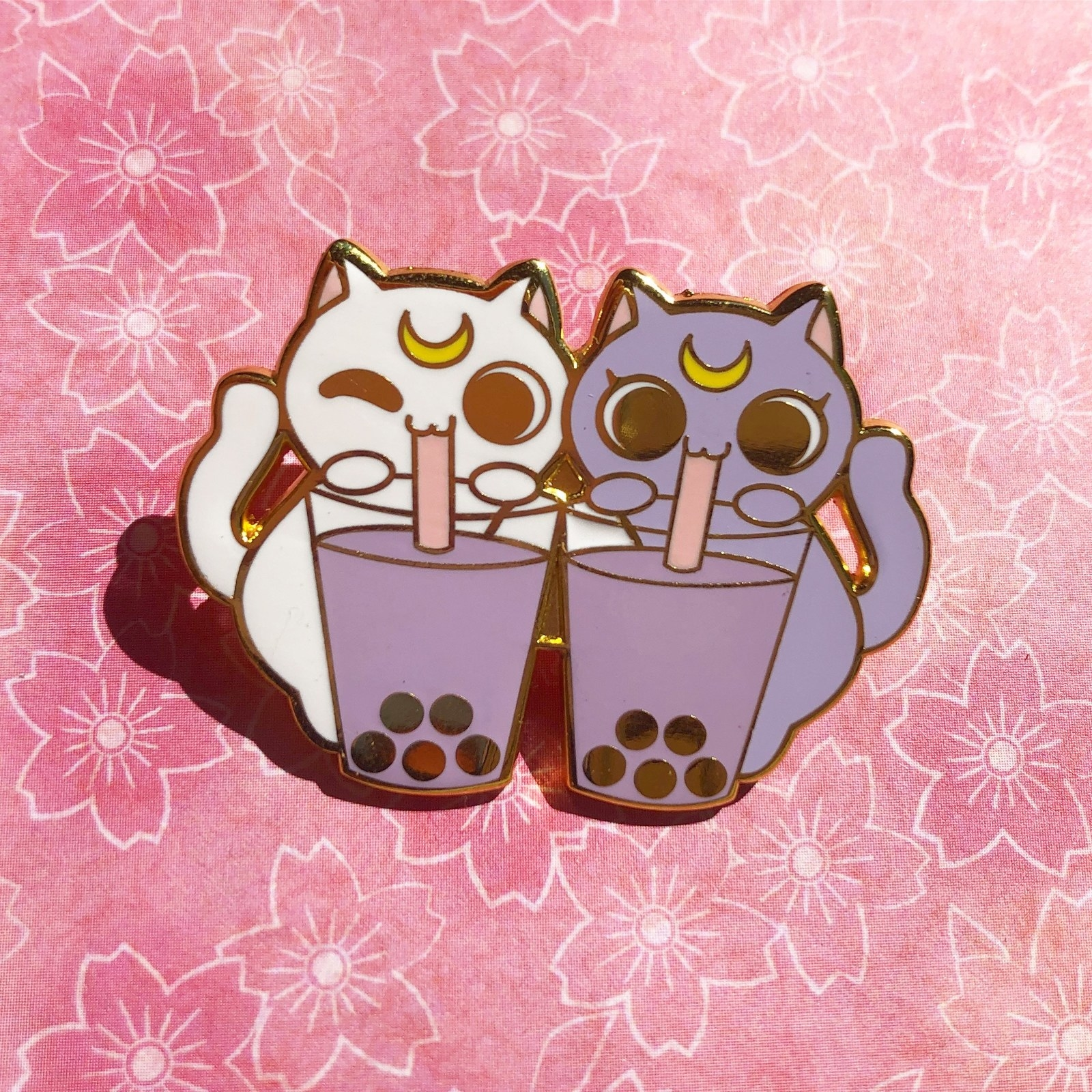 one pin of two cats drinking bubble tea