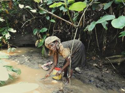 A Baka woman fishes in the forest near Lobéké National Park.