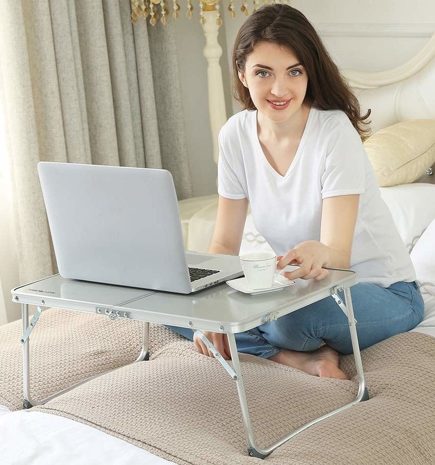 A model using the the folding desk in silver to hold a laptop and coffee mug while sitting in bed