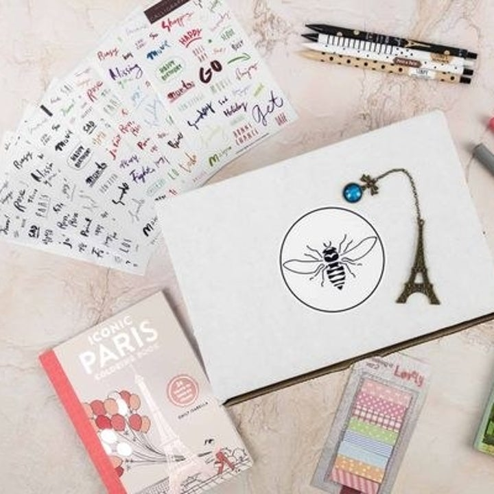 An array of stationery, planner stickers, pens, pencils, and a bookmark on top of the box
