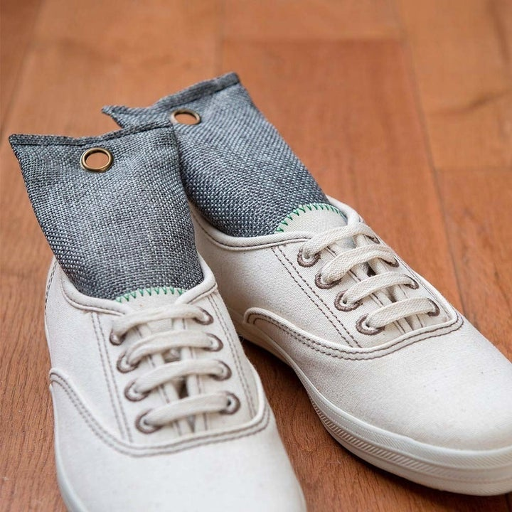 A reviewer's sneakers with the charcoal bags