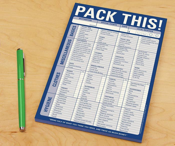 """The """"Pack This!"""" notepad check list on a counter next to a pen"""