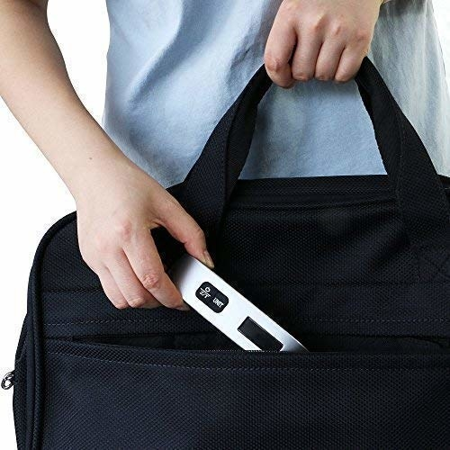 A person putting the small digital scale in their luggage bag