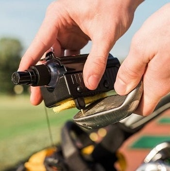 The tool removing dirt from grooves on a club