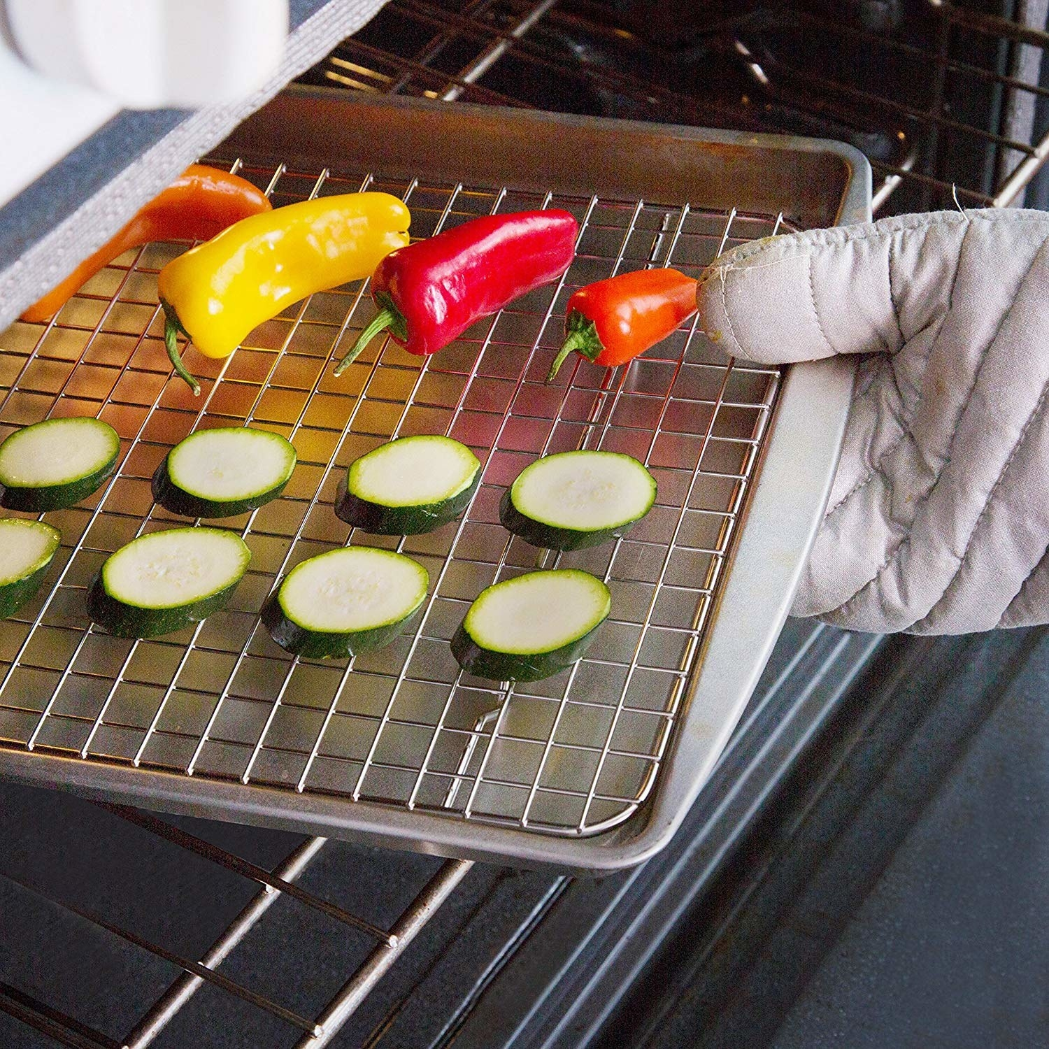 Vegetables being pulled out of the oven. They are on top of the cooling rack, on a backing sheet