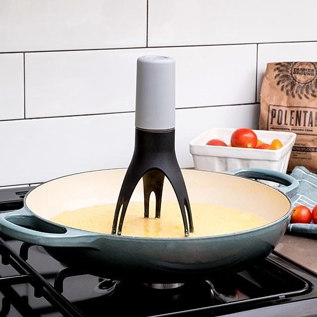 The pan stirrer with three leg-type stirrers propped up in pan to stir ingredients