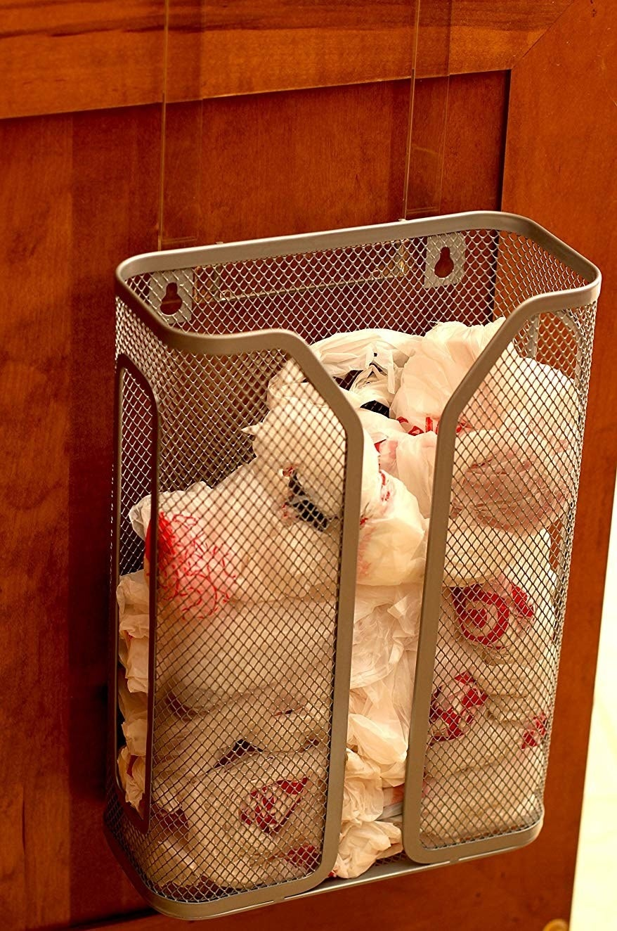 The metal mesh bag holder attached to the inside of a cabinet with a number of plastic bags inside