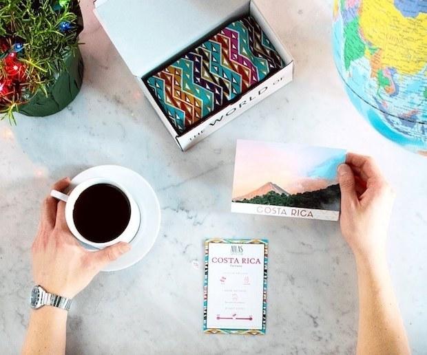 hand holds mug of coffee and postcard for costa rica