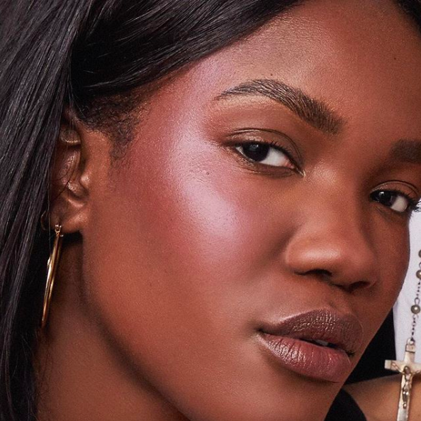 Black model wearing the pink ton highlighter on their cheekbone