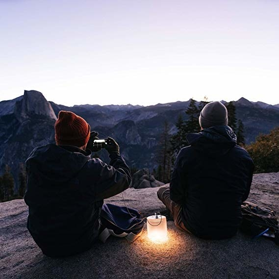 people sitting on mountain at dusk with lamp lit up