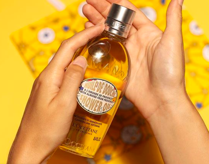 An Instagram picture of a person holding a bottle of L'Occitane The Almond Shower Oil