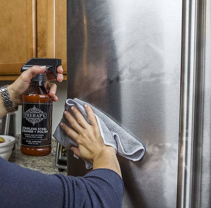 A person spraying the product on a stainless steel fridge and wiping with a rag