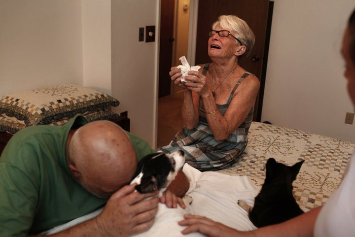 Marquita Leibe cries near her dog, Daisy, minutes after she is put to sleep. With her is her husband, Donald (left). Shortly after, he stepped outside to compose himself, overwhelmed with grief.