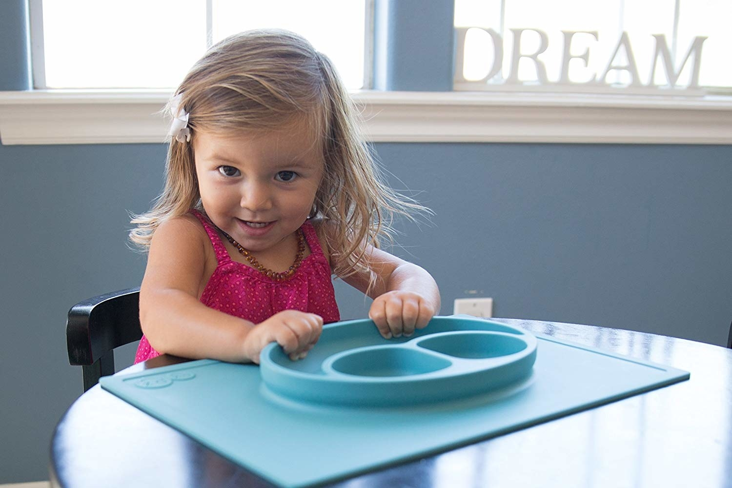 toddler sitting at table with their hands on the dinner plate/place mat that's suctioned to the table