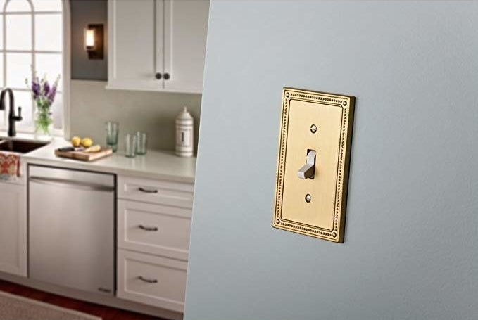 A rectangular cover over a light switch The cover has an intricate design on the border