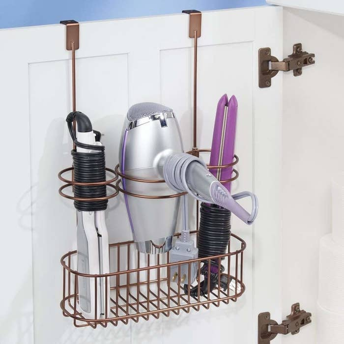 The storage rack in a brass color holding a hair dryer, flat iron, and curling iron